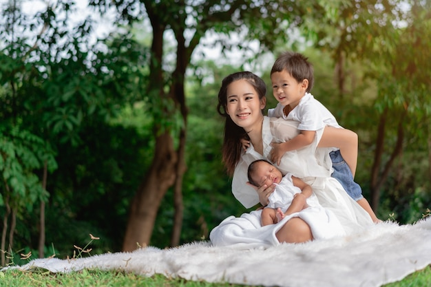 Happy loving family. asian beautiful mother and her children, new born baby girl and a boy sitting on lawn to playing and hugging in the park Premium Photo