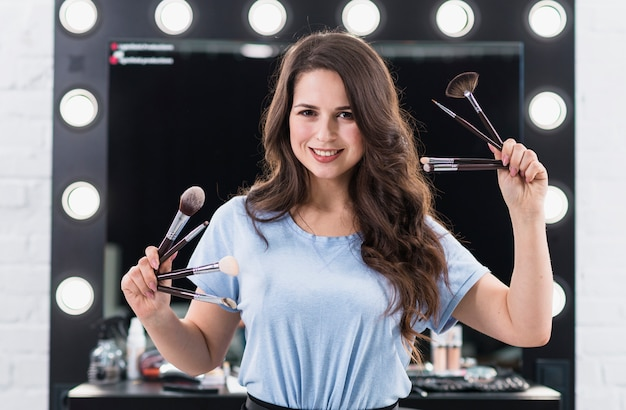 Happy makeup artist with brushes Free Photo