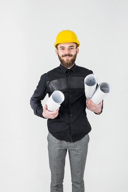 Happy male builder architect holding blueprint against white backdrop Free Photo