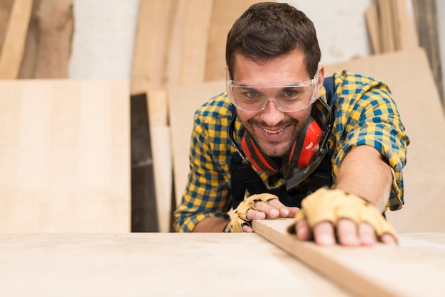 A happy male carpenter adjusting the wooden plank in the workshop Free Photo