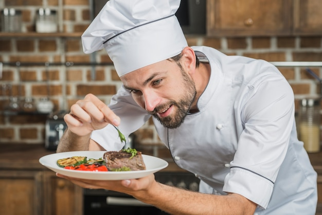 Happy male chef preparing beef steak with vegetable decoration Free Photo