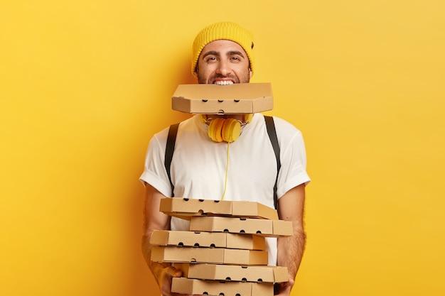 カートンピザボックスでいっぱいの幸せな男性の宅配便、段ボール容器のスタックと口の中に1つを保持し、カジュアルな服を着て、黄色の壁に隔離されています 無料写真
