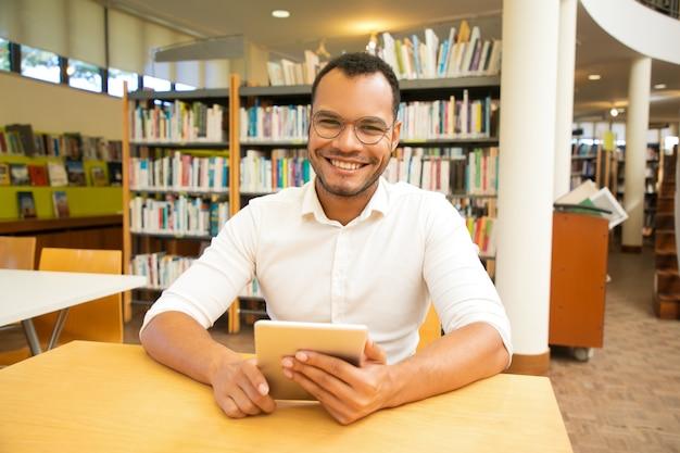 Happy male customer using public wi-fi hotspot in library Free Photo
