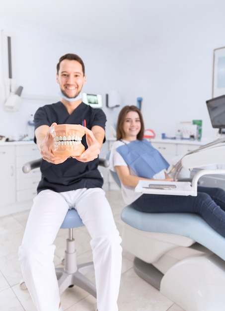 Happy male dentist showing teeth model sitting in front of female patient at dental clinic Premium Photo