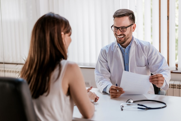 Happy male doctor discussing with patient at table in clinic Premium Photo