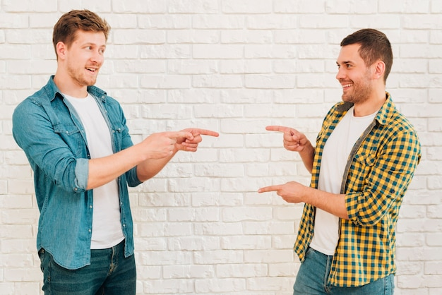Happy male friends standing against white wall pointing their fingers to each other Free Photo