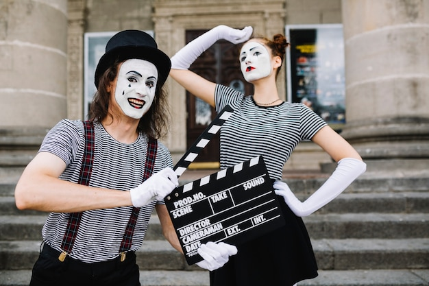 Happy male mime holding clapperboard in front of posing female mime Free Photo