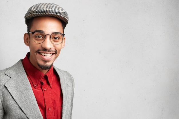 Felice studente maschio nerd o wonk indossa giacca e berretto alla moda, arriva per superare l'esame Foto Gratuite