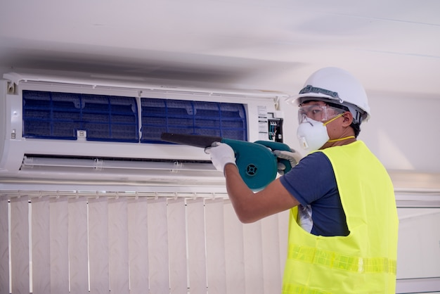 Happy male technician repairing air conditioner with safety hat and air Premium Photo