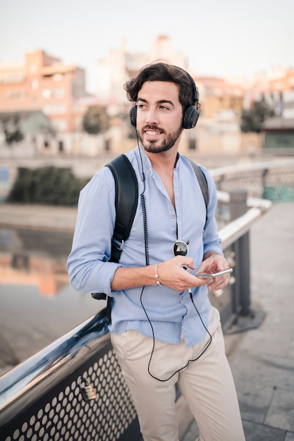 happy male tourist leaning on railing listening to music photo
