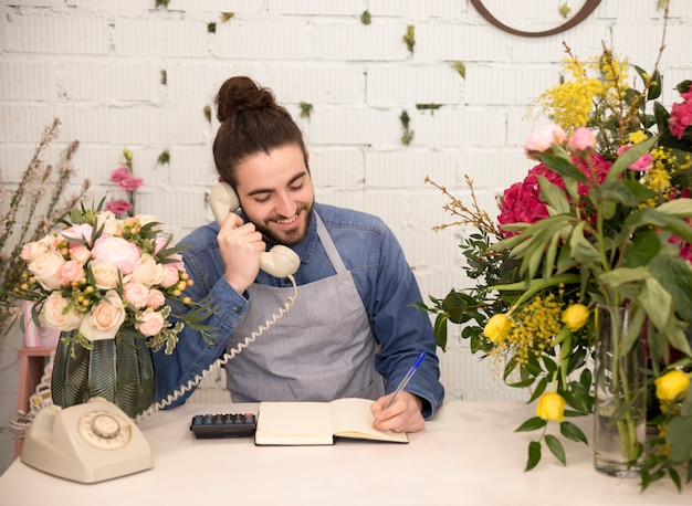 Happy male tourist taking the order on telephone in his florist shop Free Photo