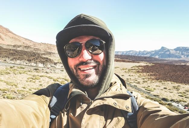 Счастливый мужской путешественник, принимая селфи портрет с горной пустыне Premium Фотографии