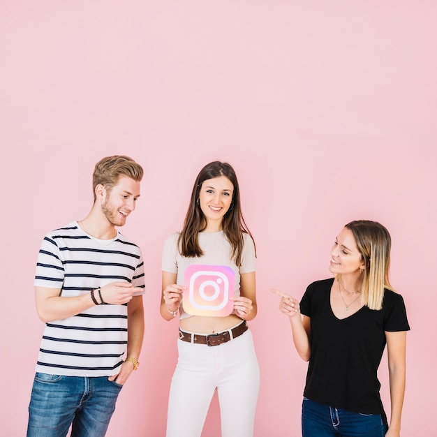 Happy man and woman pointing at their friend holding instagram icon 23 2147842213
