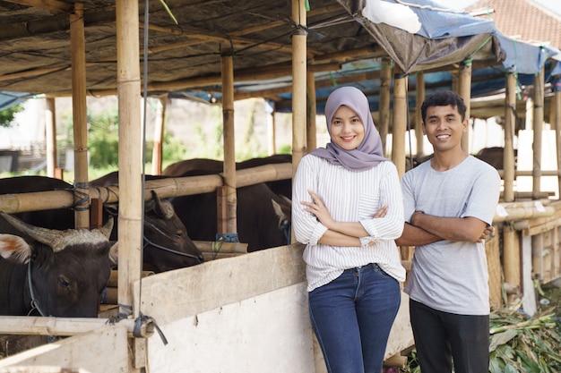 Счастливый мужчина и женщина, стоя на ферме. концепция жертвоприношения ид адха Premium Фотографии