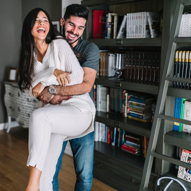 Happy man carrying her girlfriend at home Free Photo