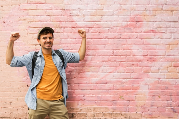 Happy man in city with pink wall Free Photo