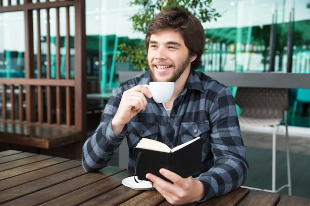 Happy man drinking coffee and reading diary in outdoor cafe Free Photo