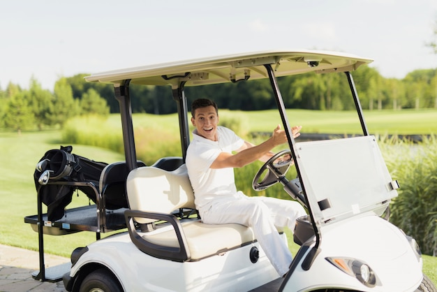 Happy man drives golf car golfer on a course. Premium Photo