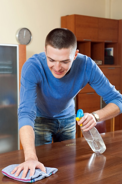 Happy man dusting  table with rag and cleanser at home Free Photo