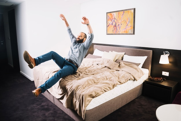 Happy man falling on bed Free Photo