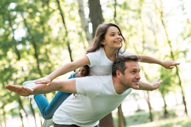 Happy man giving piggyback to his beautiful daughter with arms outstretched in park Free Photo