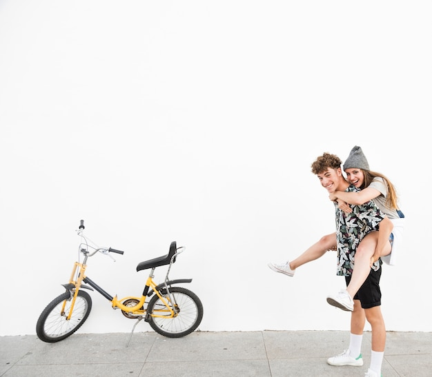Happy man giving piggyback to his girlfriend nearby yellow bicycle Free Photo