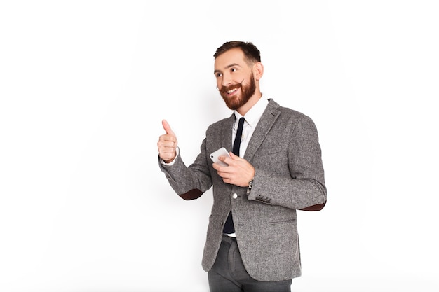 Happy man in grey suit shows thumb up holding smartphone in his arm Free Photo