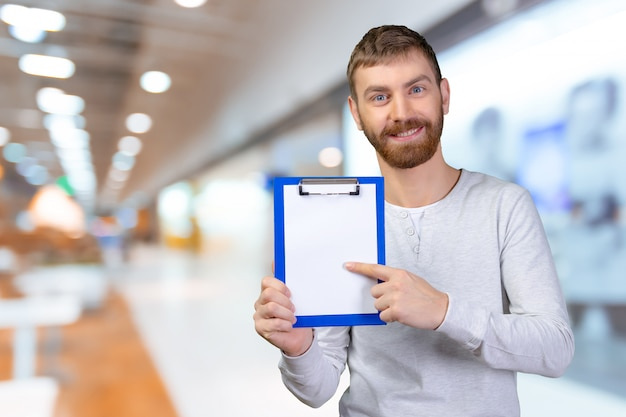 Happy man holding a clipboard and pointing with a finger Premium Photo