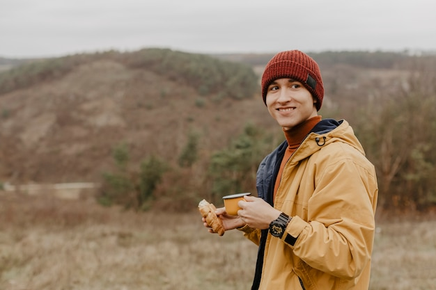 Happy man holding croissant and mug Free Photo