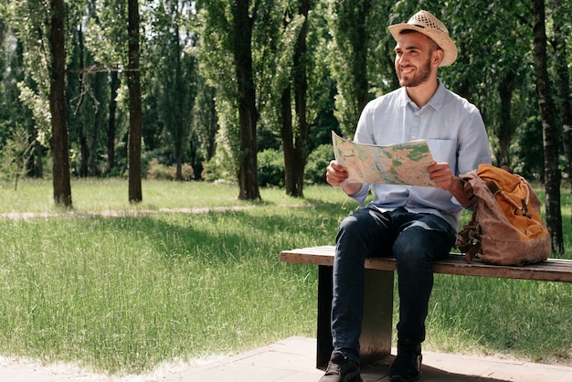 Happy man holding map sitting on bench with backpack Free Photo