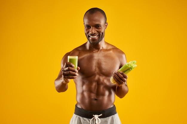 Happy man holds glass with fresh celery juice. Premium Photo