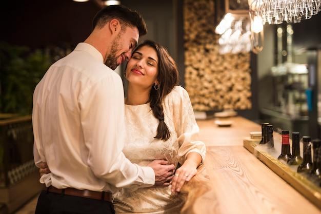 Happy man hugging cheerful woman at bar counter Free Photo