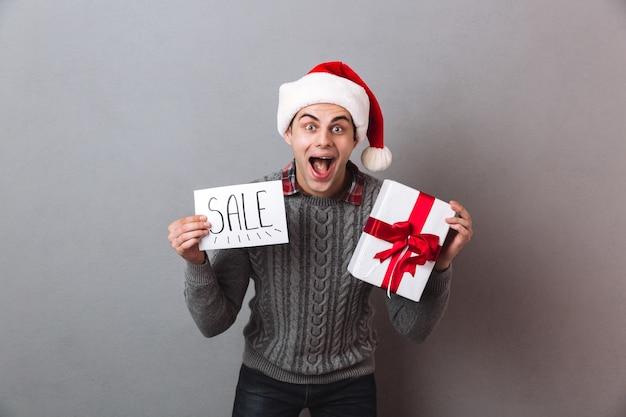 크리스마스 산타 모자 선물을 들고 행복 한 사람 프리미엄 사진