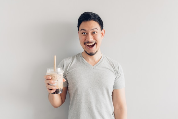 Happy man is drinking bubble milk tea or pearl milk tea. popular milk tea in asia and taiwan. Premium Photo