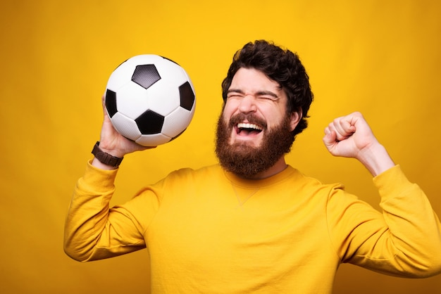 Happy man is makes winner gesture while holding a football or soccer ball. Premium Photo