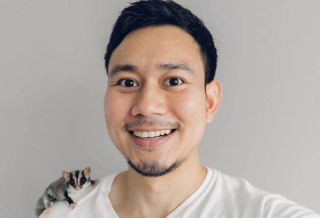 Happy man is taking selfie of himself and his sugar glider pet. Premium Photo