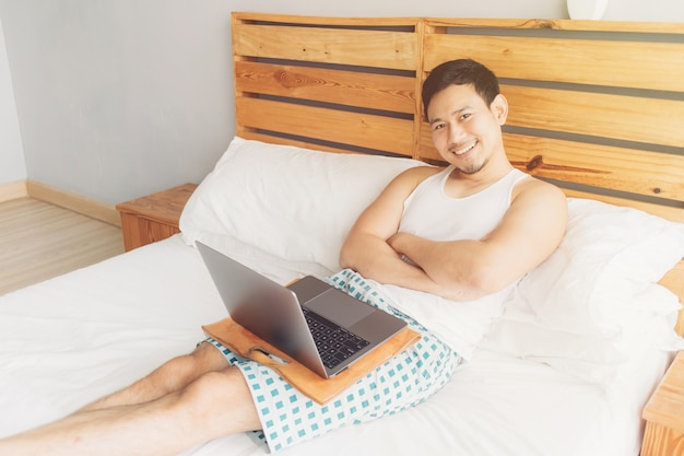 Happy man is working with his laptop on his bed. Premium Photo