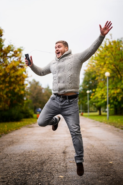 Happy man jumping up in the park Free Photo