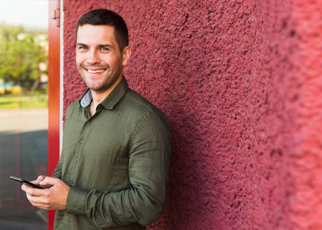 Happy man looking at camera while holding cellphone near red wall Free Photo