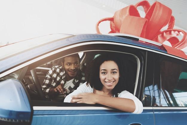 幸せな男は、夢の車を買う女に贈り物をします。 Premium写真