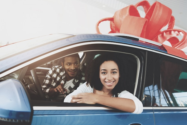 Happy man makes gift to woman buying dream car. Premium Photo