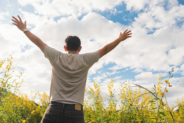 Happy man in nature of yellow field flower and bright sky white cloud Free Photo