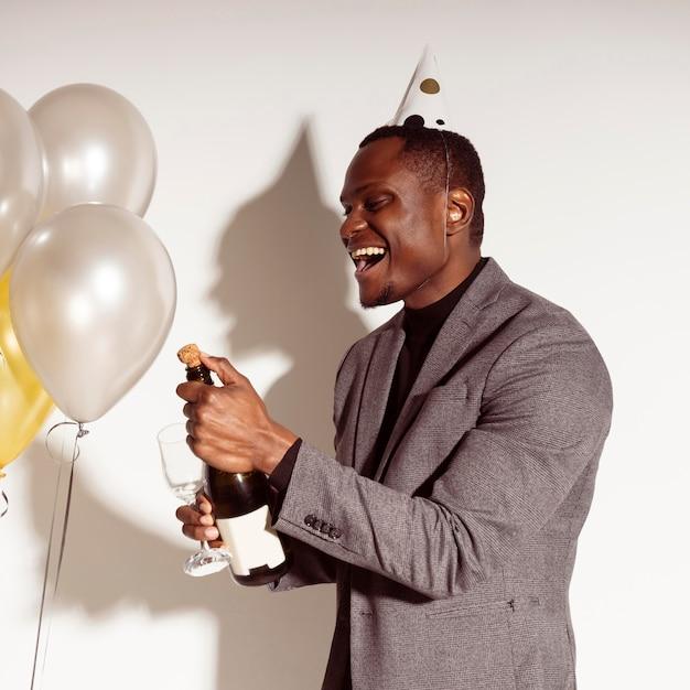 Uomo felice che apre una bottiglia di champagne Foto Gratuite