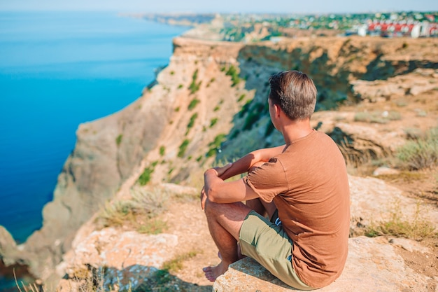 Счастливый человек на открытом воздухе на краю обрыва наслаждается видом на скалу на вершине горы Premium Фотографии