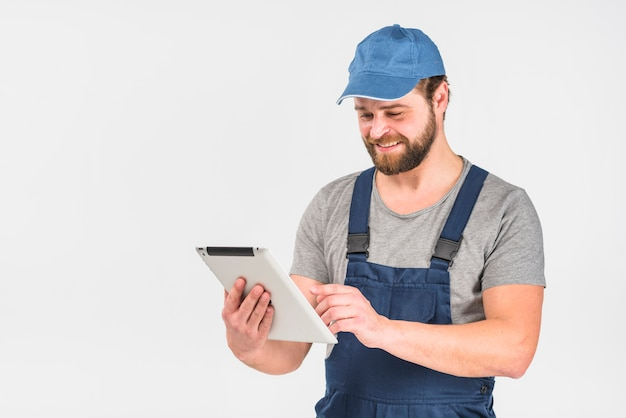 Happy man in overall using tablet Free Photo