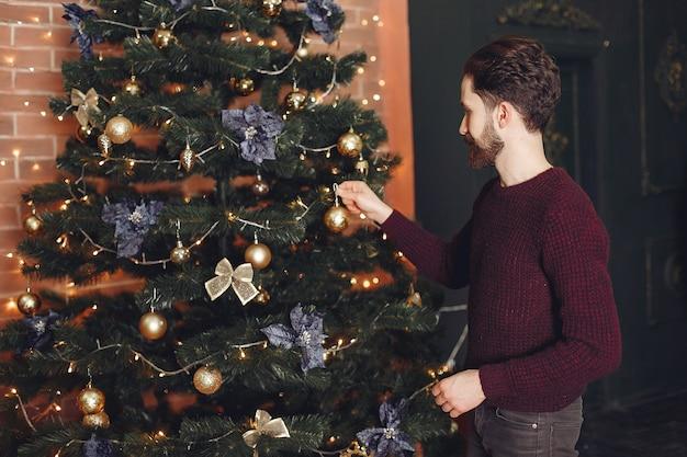 Uomo felice in maglione rosso. ragazzo davanti al caminetto. maschio sullo sfondo dell'albero di natale. Foto Gratuite