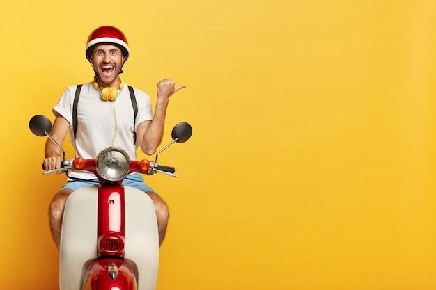 L'uomo felice guida uno scooter, mostra la direzione, punta il pollice verso destra su uno spazio vuoto su sfondo giallo, vestito con abbigliamento casual e casco, usa le cuffie, ha un'espressione del viso allegra Foto Gratuite