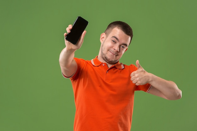 L'uomo felice che mostra a schermo vuoto del telefono cellulare contro il verde. Foto Gratuite