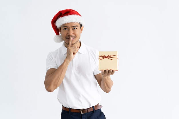 Happy man showing gift box and silence gesture Free Photo