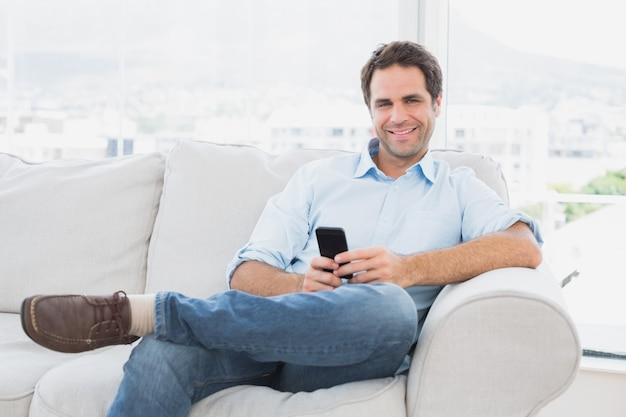 Happy man sitting on the couch using his smartphone Premium Photo